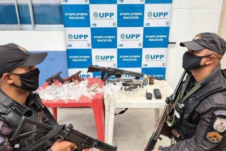 Dois PMs armados aparecem no primeiro plano, no fundo uma mesa com armas e drogas