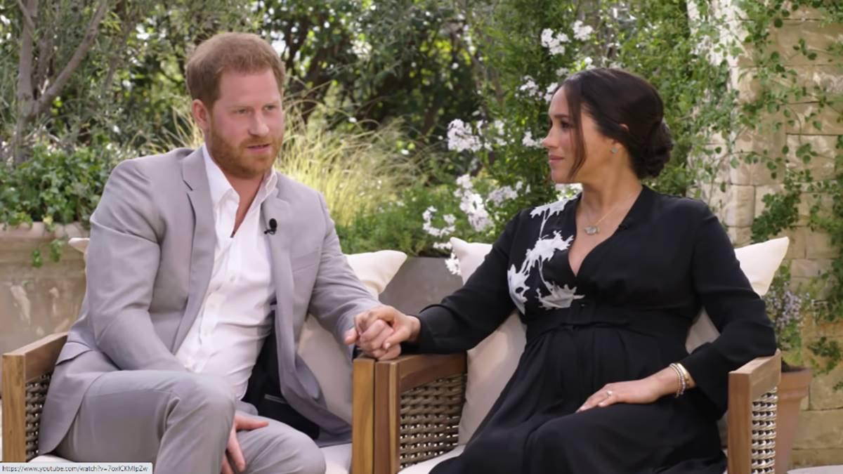 Príncipe Harry e Meghan Markle sentados em cadeiras de mãos dadas