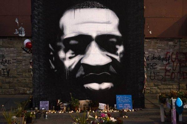 Velas e um mural com o rosto de George Floyd