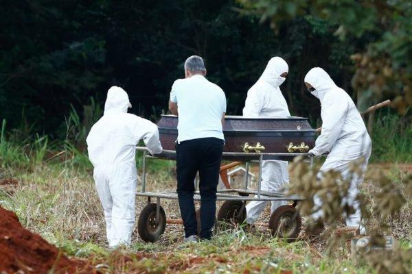 coveiros vestindo roupas especiais enterram vítima da covid-19 em cemitério de goiânia, goiás