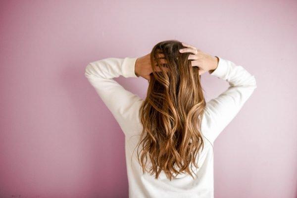 mulher passa as mãos no cabelo
