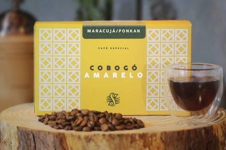 Caixa de café apoiada em uma tora de madeira com grãos e uma xícara de café