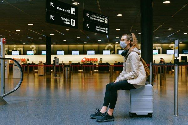 mulher sentada em uma mala no aeroporto usando máscara de proteção contra a covid coronavírus