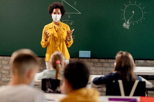 professora dando aula com máscara de proteção