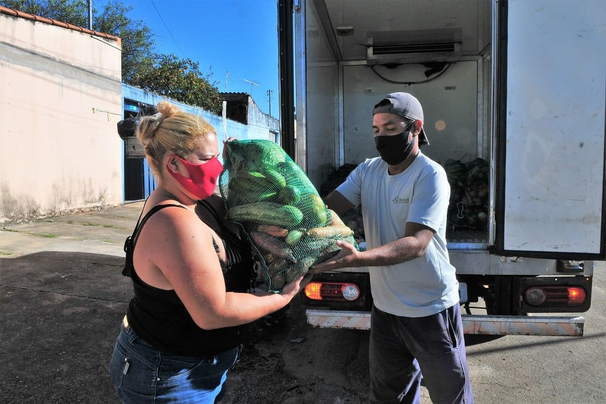 mulher recebe cesta de alimentos usando mascara de proteção contra a covid-19
