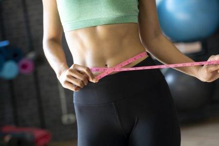 Mulher com fita métrica na barriga