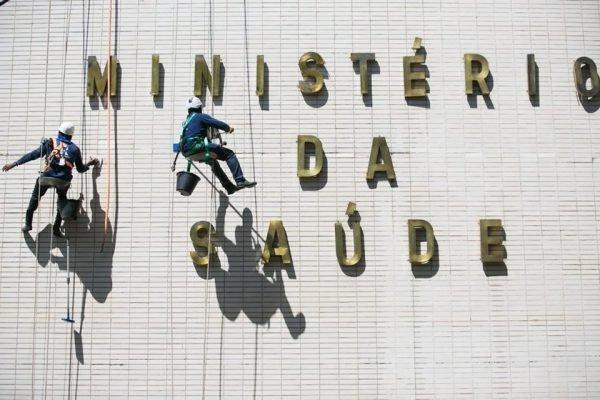 Ministério da Saúde com operários limpando letreiro
