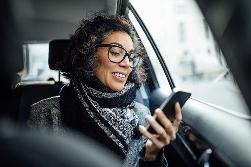Mulher mexendo no celular no carro