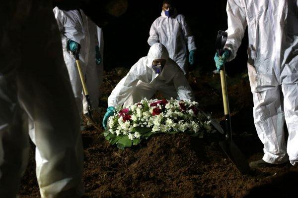 Sepultadores enterram à noite corpo de vítima de Covid-19 no Cemitério da Vila Formosa, em São Paulo