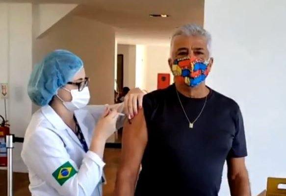 Lulu Santos sendo vacinado contra a Covid-19 no Rio, por profissional de saúde, de máscara