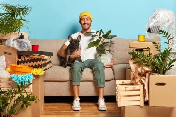 cachorro e homem num sofá rodeados de plantas