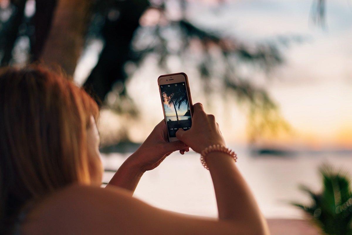 mulher usa o celular para tirar foto do por do sol