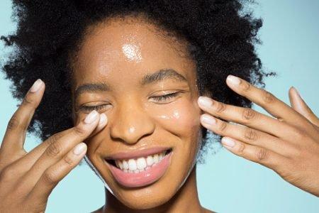 mulher aplicando maquiagem glossy