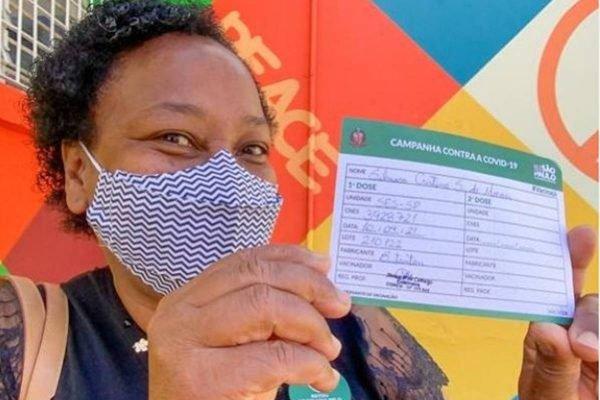 Merendeira Silmara Moraes com cartão de vacina após receber primeira dose de vacina contra a Covid-19