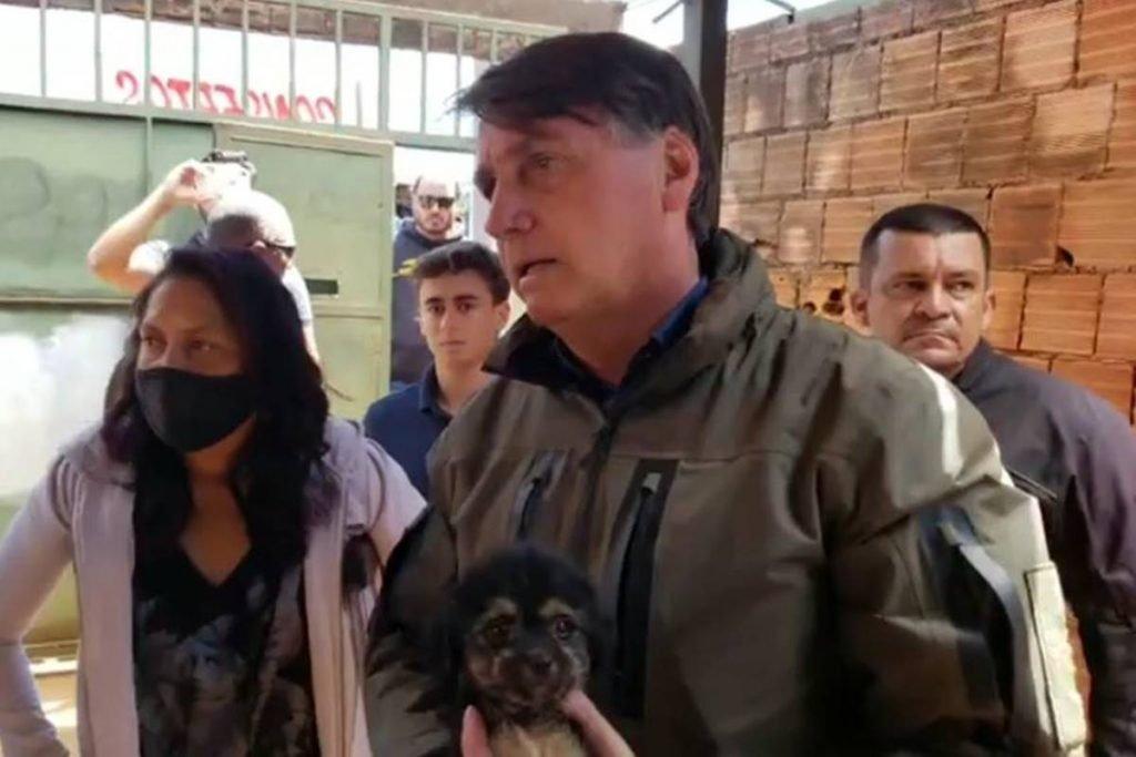 Jair Bolsonaro segura cachorro durante conversa com venezuelanas