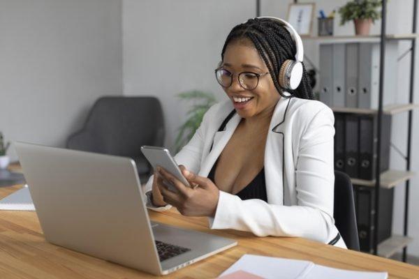 Mulher trabalhando com celular na mão e fone de ouvido