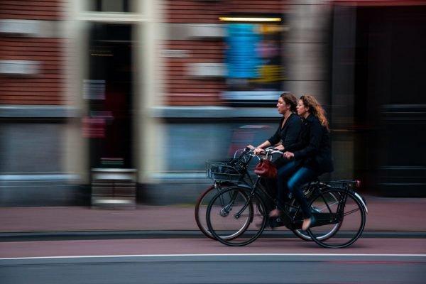 mulheres andando de bicicleta em uma ciclovia