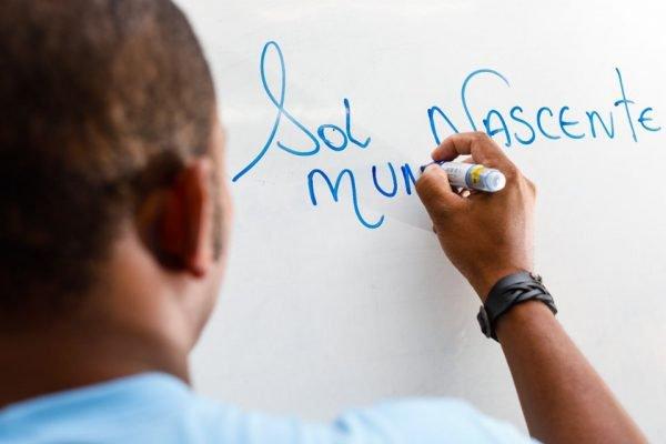 Homem de camisa azul escreve Sol Nascente em quadro branco