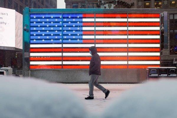 pessoa de máscara em frente à bandeira dos eua