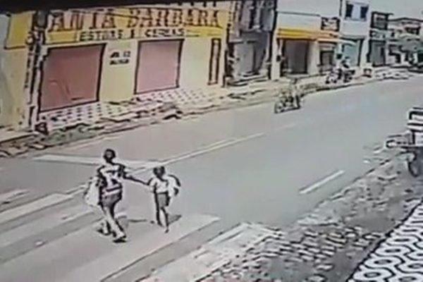 mulher e criança atravessam faixa