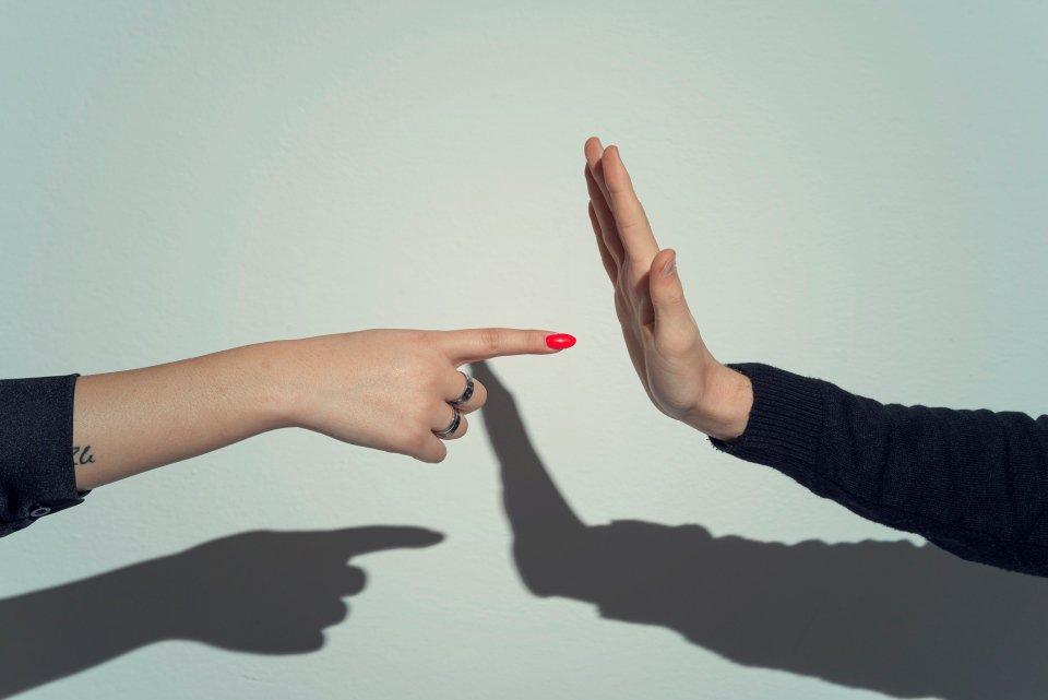 dedo acusando e mão evitando