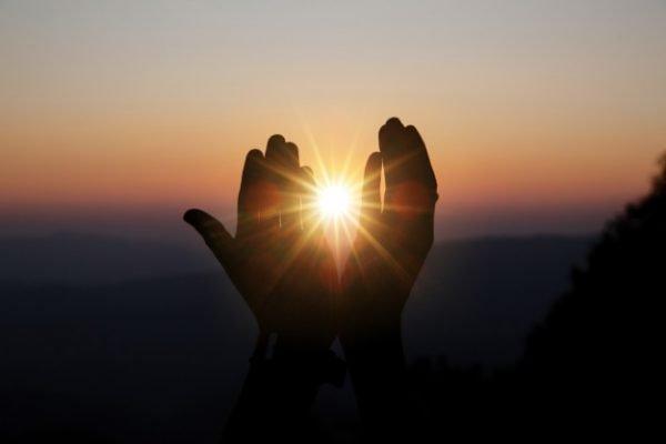 Mão de homem com sol