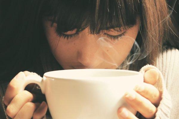 menina cheirando xícara de café