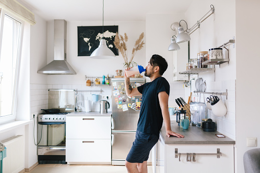Homem tomando suplemento na cozinha