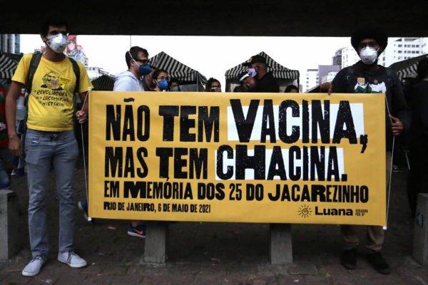 Manifestantes com faixa escrito NÃO TEM VACINA, MAS TEM CHACINA