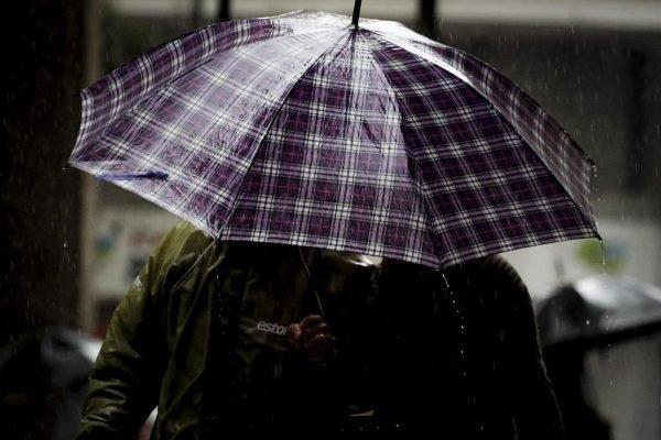 Pessoa se protege da chuva