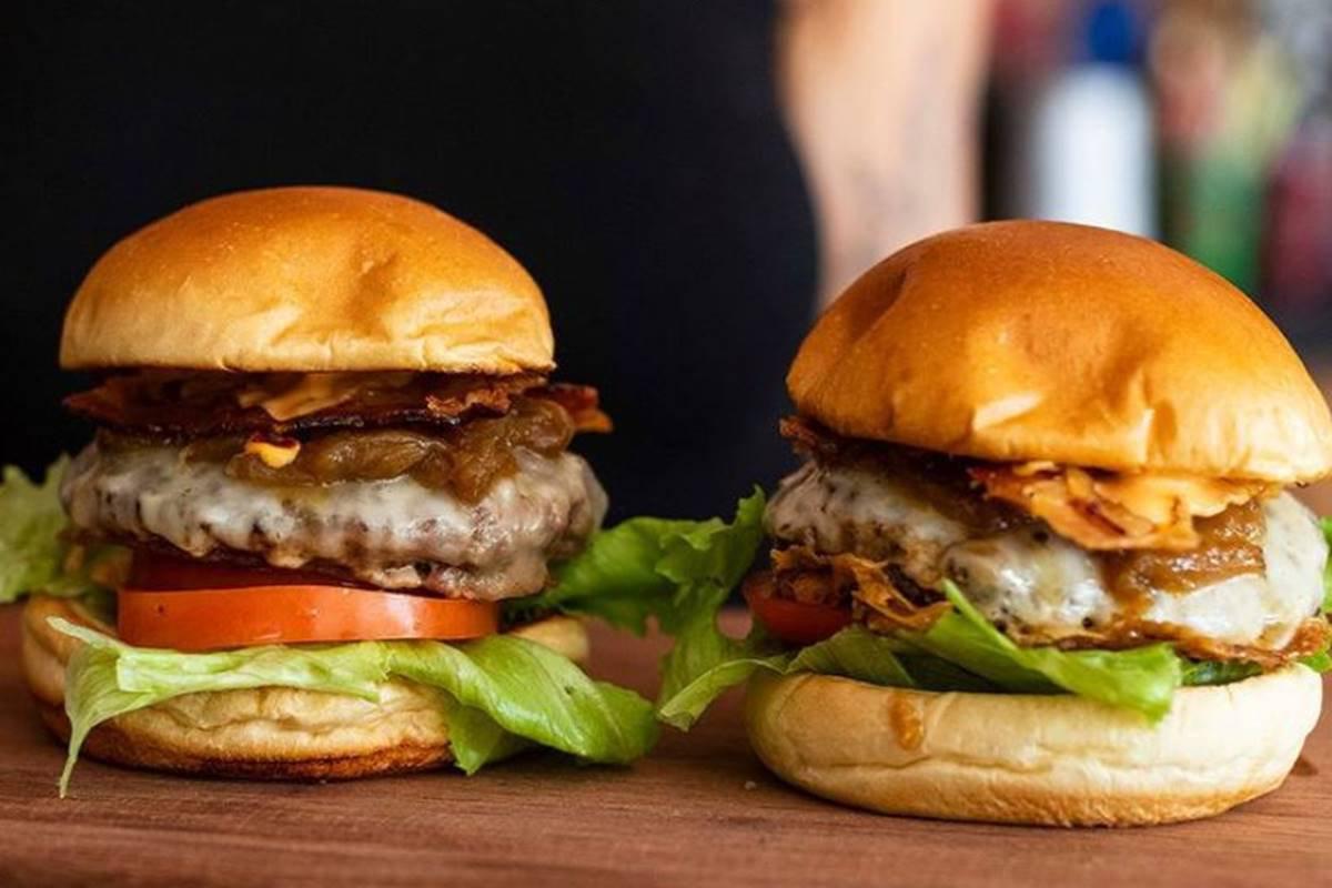 Dois hambúrgueres completos em cima de uma tabua de madeira