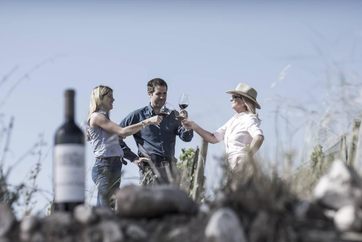 Três pessoas brincam e um vinho aparece em cima das pedras, a frente, em perspectiva