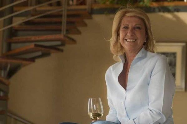 Mulher sorri com uma taça de vinho na mão