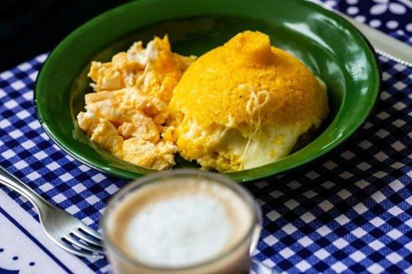 Prato com cuscuz com queijo e ovo e um copo de café com leite ao lado