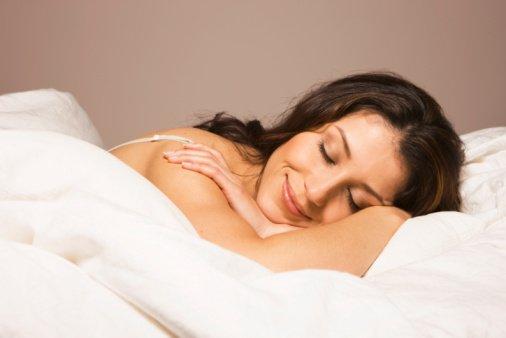 mulher dormindo na cama e sorrindo