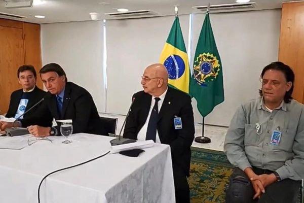 Reunião de Jair Bolsonaro com médicos, na qual ouve ressalvas às vacinas; na mesa, Osmar Terra ao lado de Bolsonaro, com o virologista Paolo Zanoto sentado à direita, na foto, de camisa cinza e cabelos longos