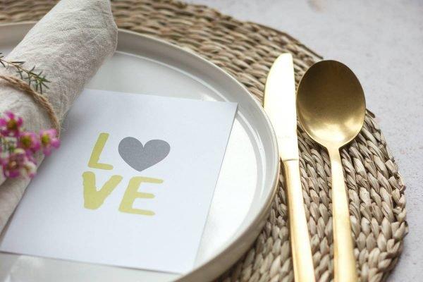 Prato e talheres montados para jantar com cartão escrito love