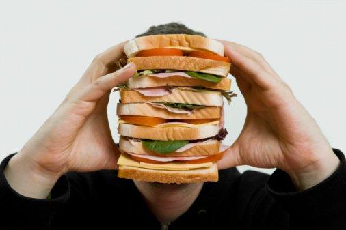Homem segurando sanduíche