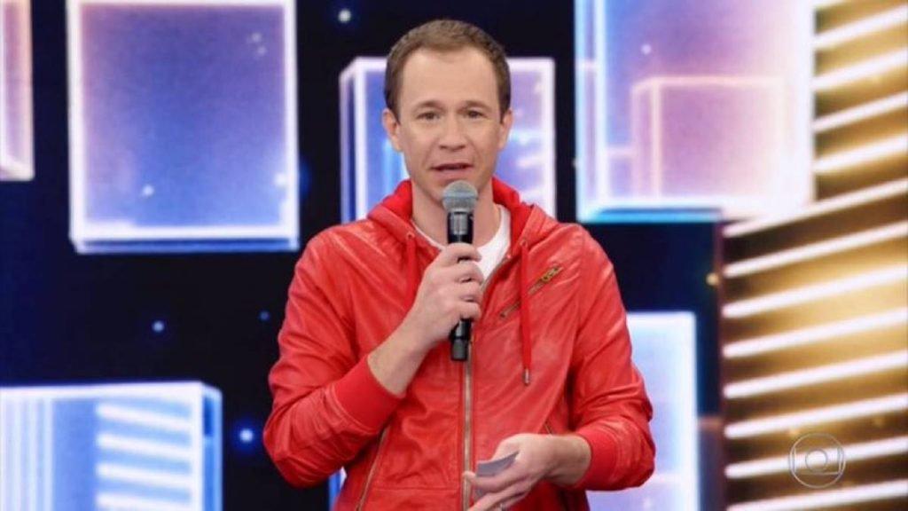 Tiago Leifert de blusa de frio laranja com microfone na mão no programa Domingão