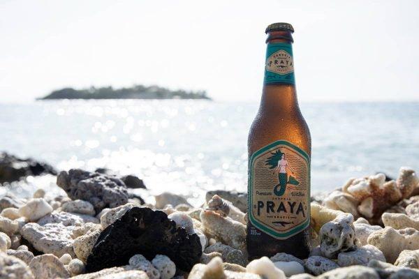 Cerveja em meio a pedra com mar de fundo