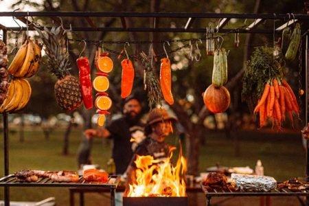 Parrilla com frutas, legumes e carne e duas pessoas ao fundo