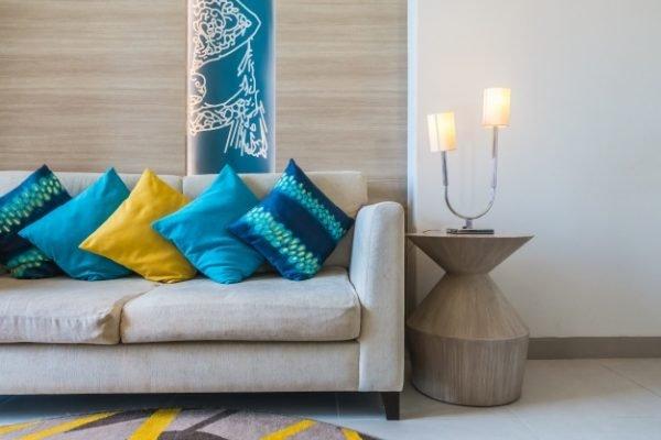 Parte de um sofá com almofadas em tons de azul