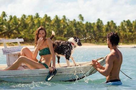 Casal em barco com cachorro, para campanha da Havaianas