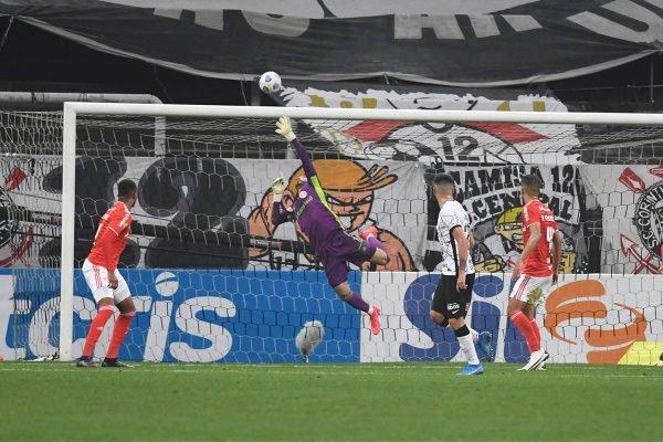 Jogadores olham para goleiro enquanto ele tenta pegar a bola