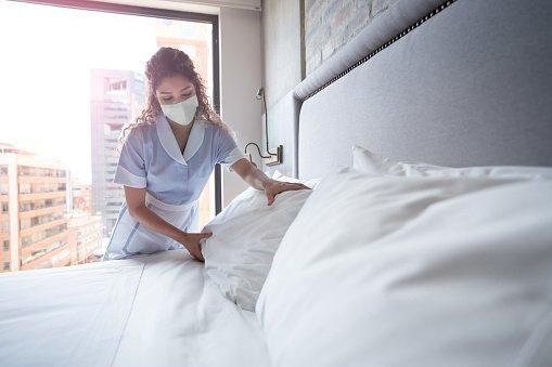camareira arrumando a cama em hotel de máscara