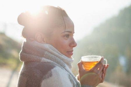 mulher bebendo chá no frio