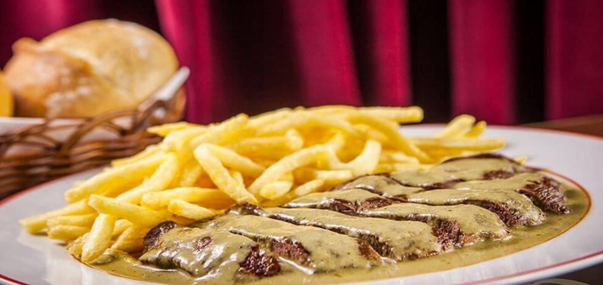 Prato com entrecote coberto de molho e batatas fritas