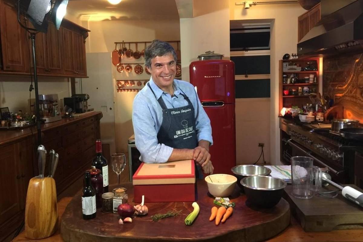 Chef Olivier Anquier apoia um braço em cima de uma caixa sobre mesa com ingredientes e utensilios