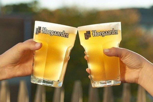 Duas mãos brindando com corpos de cerveja