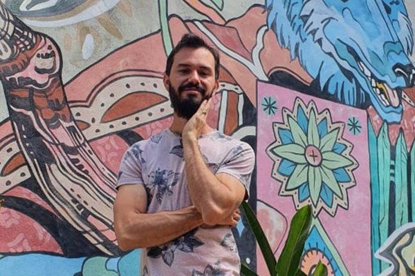 Chef Lui Veronese sorri com mão no rosto em frente a uma parede colorida com desenhos
